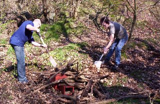 Lee and Jaymie move leaf litter over the logs that everyone has added.